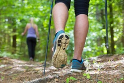 Young fit couple hiking in nature. Adventure, sport and exercise. Detail of male step, legs and nordic walking poles in green woods.