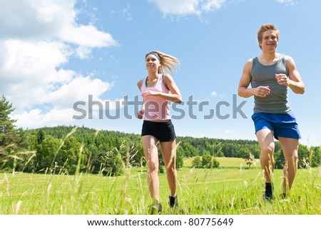 Young fit couple jogging on summer day in meadows countryside - stock photo