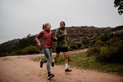Young fit couple laughing while running on gravel mountain track in cloudy weather with luscious bushes