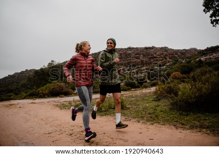Young fit couple laughing while running on gravel mountain track in cloudy weather with luscious bushes Stockfoto ©
