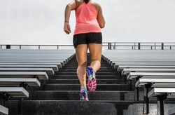 Young fit female athlete running up bleachers at a stadium to illustrate