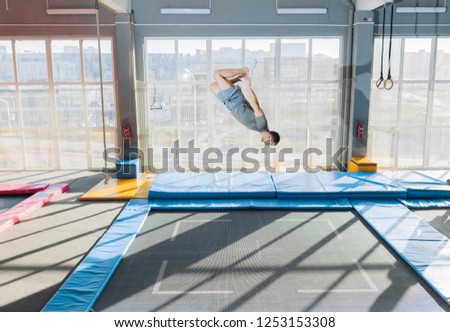 young fit flexible guy doing complex somersault on the trampoline. full length side view shot. copy space. stunt at sky park #1253153308