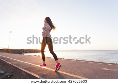 Young fit girl athlete running on a sunset along seaside on running path in summer. Wearing sportswear. Activity and healthy lifestyle in a city concept #429025633