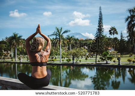 Young fit girl practising asana and meditation during her yoga retreat luxury vacation in Bali