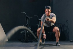 Young fit handsome muscular man in activewear working out heavy battle rope at the gym. Motivation concentration endurance exercise.