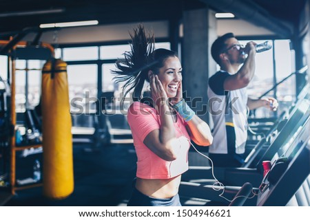 Young fit man and woman running on treadmill in modern fitness gym.