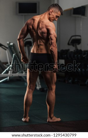 Young fit man doing bodybuilding competition poses
