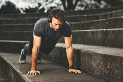 Young fit man doing push-ups outdoors on concrete steps