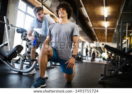 Young fit man doing workout with a personal trainer.