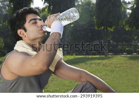 Young fit man drinking water after sport workout