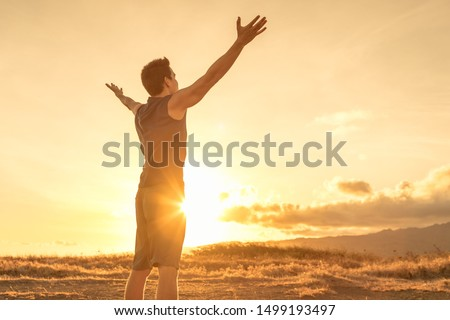 Young fit man felling hopeful, energized, and rejuvenated standing in a beautiful outdoor setting. Foto stock ©