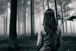Young fit runner girl standing front of a scary horror forest in black and white