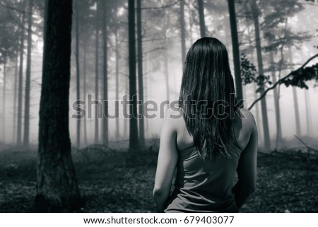 Young fit runner girl standing front of a scary horror forest in black and white #679403077