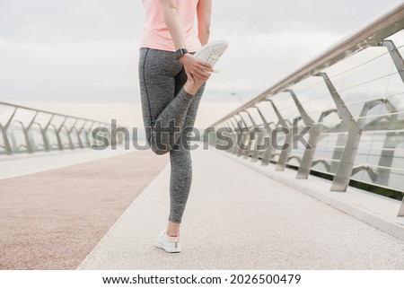 Young fit slim sportswoman female athlete stretching her legs before jogging running on city bridge in urban area in sporty fitness clothes and trainers. Warming-up exercises outdoors. Foto stock ©