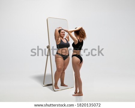 Young fit, slim woman looking at fat girl in mirror's reflection on white background. Thinking she's not enough sportive. Concept of healthy lifestyle, fitness, sport, nutrition and body positive. Foto stock ©