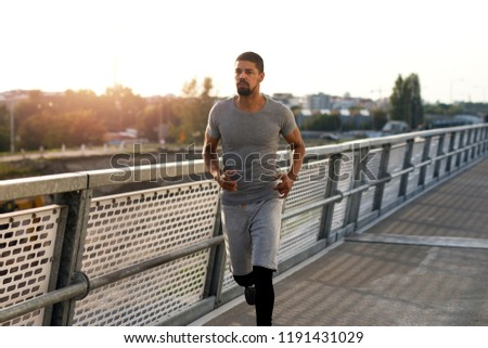 Young fit sportsmen running over bridge in the city. Urban training and healthy lifestyle.