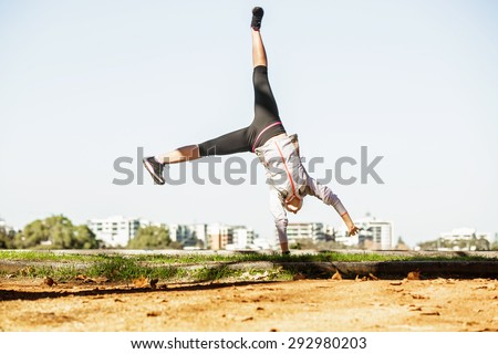 Young fit sporty woman doing simple acrobatics exercise routine in autumn park with city at background