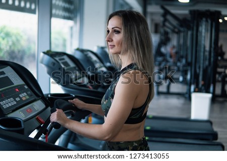 Young fit woman doing running exercise in gym at treadmill speedwalk running road. #1273413055
