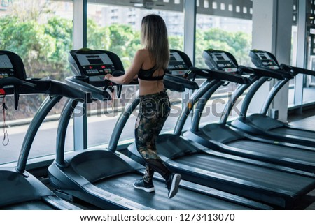 Young fit woman doing running exercise in gym at treadmill speedwalk running road. #1273413070