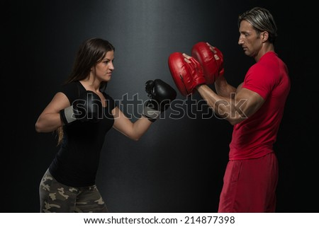 Young Fit Woman Fighting A Man - Bodybuilding Couple Posing With Boxing Gloves On Black Background