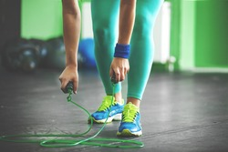 Young fit woman is taking jumping rope.