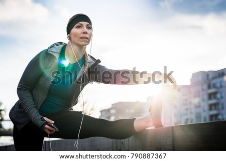 Young fit woman looking away with determination while stretching her leg during outdoor warming up routine in the city in a sunny day #790887367