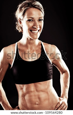 Young fit woman posing against black background - stock photo