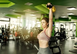 Young fit woman practices bench press with one hand with kettlebell in the gym
