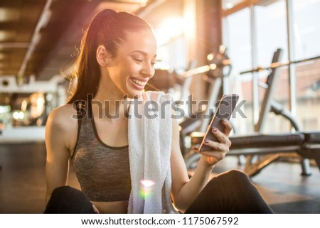 Young fit woman using smartphone at gym