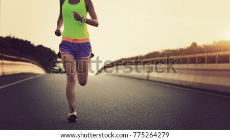 young fitness asian woman runner running on city road #775264279