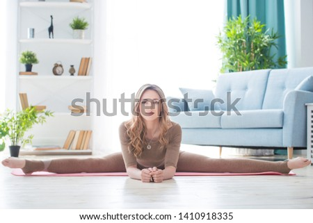Young fitness beautiful woman female doing sport exercise and sit on splits twine on yoga mat in morning. Healthy lifestyle, morning workout concept