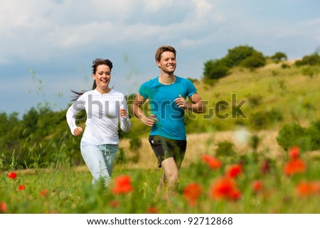 Young fitness couple doing sports outdoors; jogging on a green meadow in summer under a blue sky