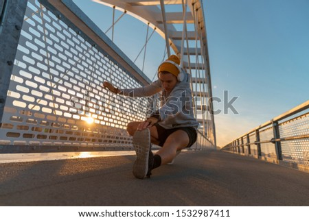 Young fitness male doing morning workout rutine on bridge outdoors. Healthy Lifestyle. Cardiovascular workouts - Stock Image