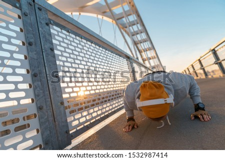 Young fitness male doing morning workout rutine on bridge outdoors. Healthy Lifestyle. Cardiovascular workouts. Push ups - Stock Image