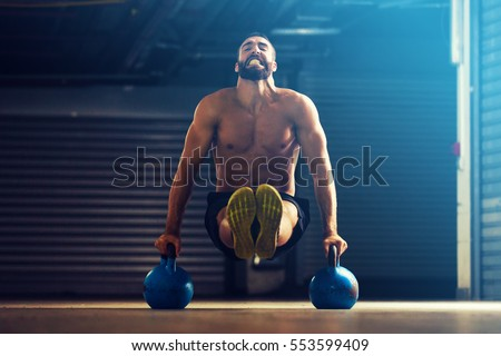 Young fitness man is training by kettlebell. #553599409