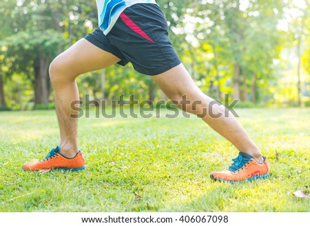 young fitness man runner stretching legs before run #406067098