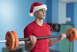 Young fitness Santa Claus training in gym lifting weights
