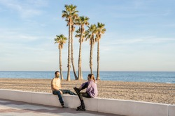Young fitness skateboarding couple in medical protective mask talking , sitting on promenade at the seaside with palm trees and beach background.Healthy lifestyle, coronavirus, covid-19 concept