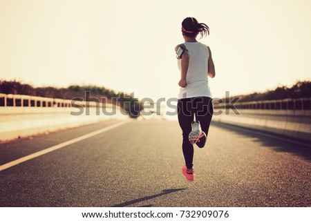 Young fitness sport woman running on city road