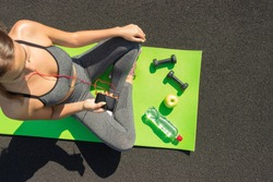 Young fitness sportswoman sitting and using smartphone in gym. Girl on yoga mat with botte of water, dumbbell and ealthy apple listens to music. Sports and healthy concept. top view.