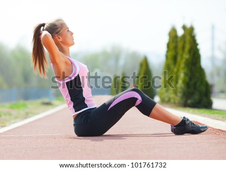 Young fitness woman doing exercises outdoor. - stock photo