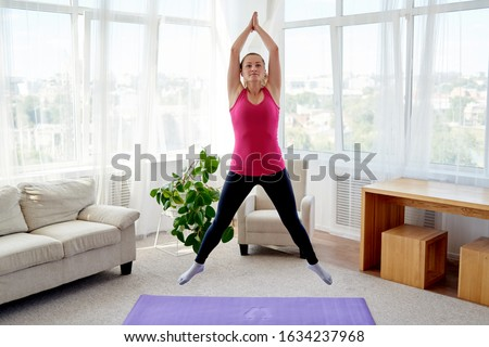 Young fitness woman doing jumping jacks or star jump exercise at home, copy space. Girl working out, full length portrait. Healthy lifestyle concept