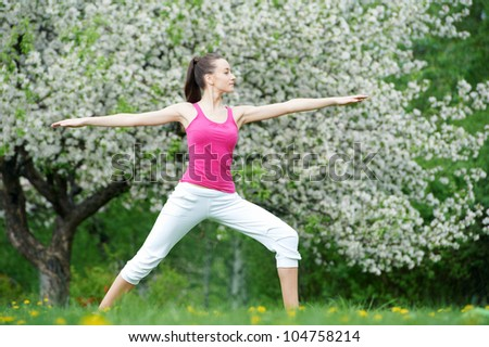 Young fitness woman doing physical stretching exercises during outdoors sport training