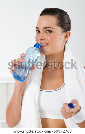 young fitness woman drinking water after workout