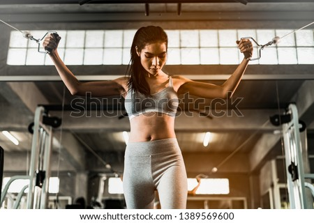young fitness woman execute exercise with exercise-machine in gym, horizontal photo.Doing Workout Exercises.Relaxing After Fitness Training in gym.