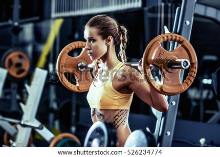 young fitness woman execute exercise with weight in gym, horizontal photo