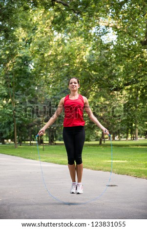 Young fitness woman exercising - jumping with skipping rope