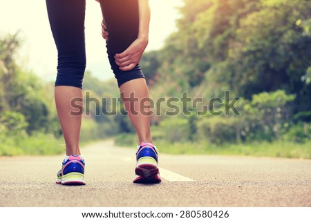 young fitness woman jogger hold her sports injured leg at forest trail  #280580426