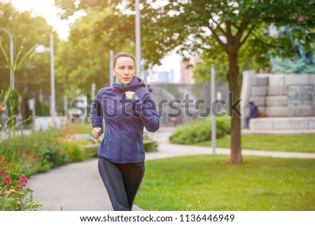 Young fitness woman jogging in park in the sunny morning. Image with copy space #1136446949