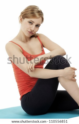 young fitness woman making a pause sitting on a blue mat on white background